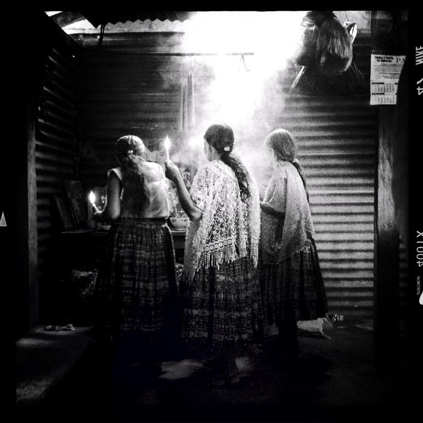 Mujeres maya q´eqchi´preden candelas durante el velorio de Agustín Tec Pop. Los restos de Tec Pop fueron exhumados en una fosa clandestina dentro la antigua zona militar 21 en la ciudad de Cobán.