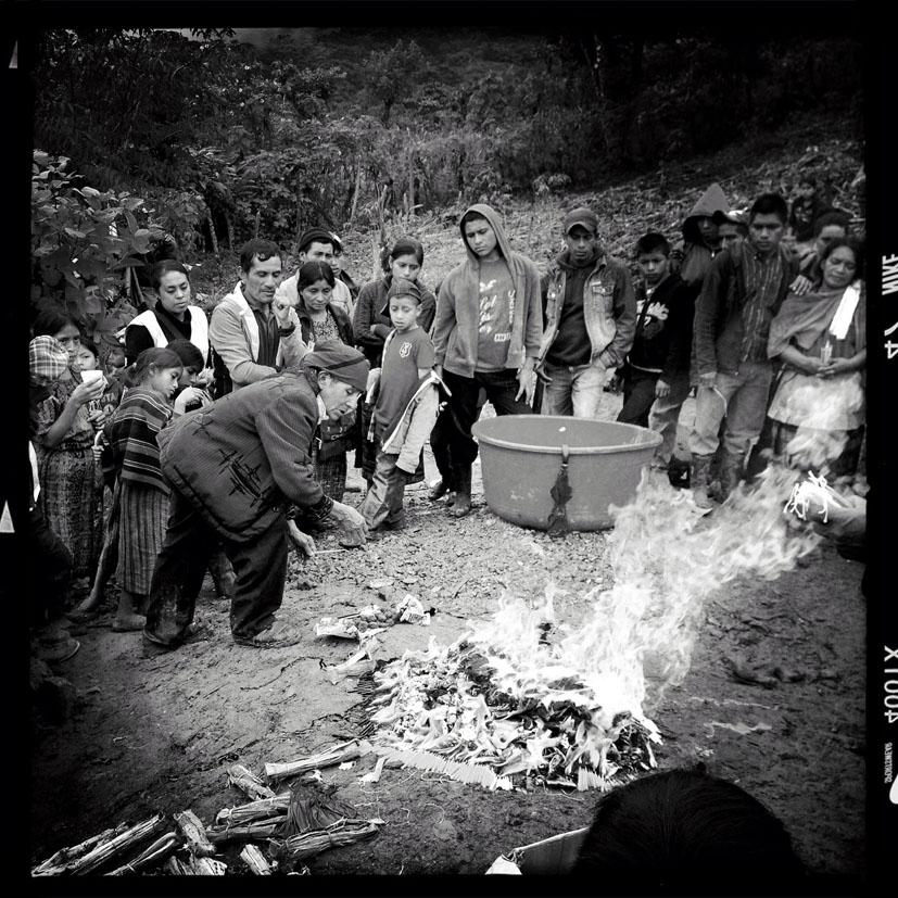 Andrés Ramírez, 70, guía espiritual maya ixil, lidera una ceremonia maya durante el entierro de 77 víctimas de la masacre de Covadonga.