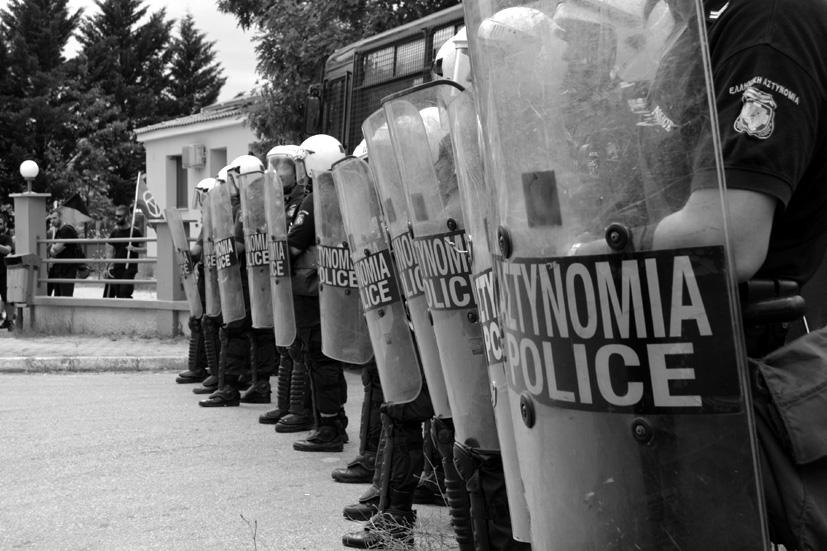 """Una treintena de policías helenos esperan parapetados tras los escudos la llegada de las y los manifestantes del campamento """"No Borders"""" al centro de detención de Paranesti."""